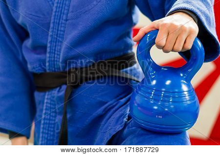 Close Up of Woman in Blue Judo Gi and Black Belt which is Train with weights and kettlebells Girya