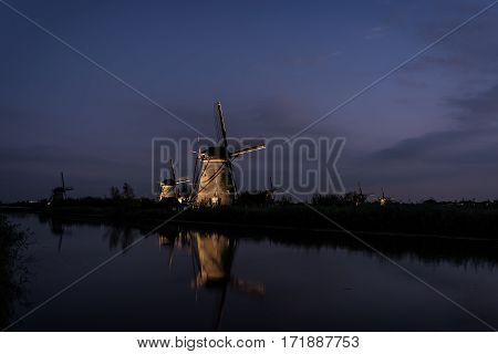 Several illuminated windmills with reflection in the water of the river at twilight in the beginning of the night in Kinderdijk the Netherlands. This windmill landscape is an UNESCO world heritage site. frequented by tourists and close to Rotterdam.