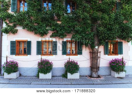 Typical Austrian Alpine house with bright flowers on the balcony and trees, Hallstatt, Austria, Europe