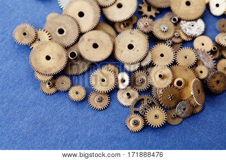 Vintage cogs wheels gears collection on blue textured paper background. macro view shallow depth of field photo