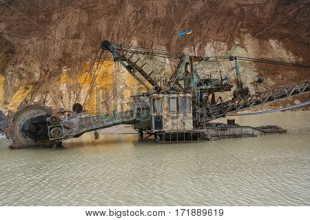 Clay quarry near the town of Pology in the Zaporizhya region of Ukraine flooded heavy rains. Equipment for mining of refractory clay -excavator rotary electric ЭР
