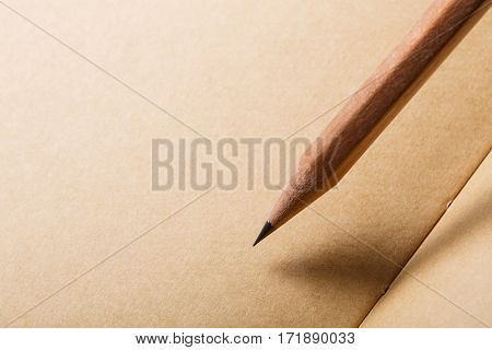 brown paper background with brown pencil on diagonal and empty place for text. Educatio, school and student, Writing, painting and drawing. Office suppiels.