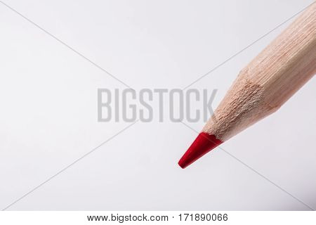 red pencil draws or writing on white paper sheet. Sharpen pencil. Education and school. Colorful pencil. Wooden. Office suppiels.
