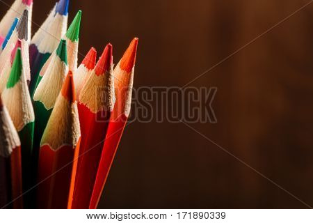 different pencils on the brown wooden table background. Colorful pencils. School and education. Drawing and painting. NAtural materials. Brown background.