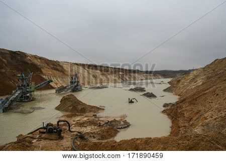 The flooded clay quarry. Clay quarry near the town of Pology in the Zaporizhya region of Ukraine flooded heavy rains. Equipment for mining of refractory clay - excavator rotary electric . March 2006