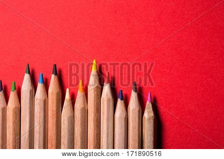 line of colored pencils on bright red background. Creative location. Irregularity. Art and design. Idea and concept. Drawing and painting.