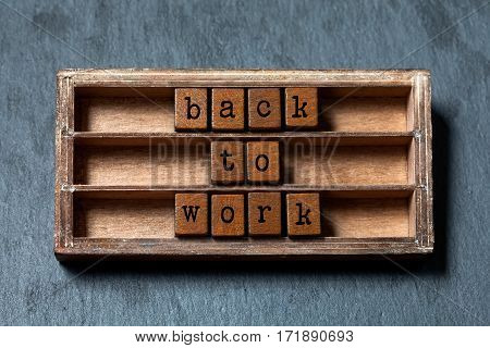 Back to work. Positive motivational quote. Vintage box, wooden cubes phrase with old style letters. Gray stone textured background. Close-up, up view, soft focus photo