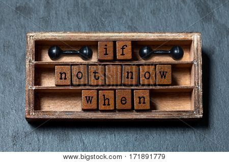 If not now when. Motivation and success future management quote. Vintage box, wooden cubes with old style letters, ancient dumbbells. Gray stone textured background. Close-up, up view, soft focus.