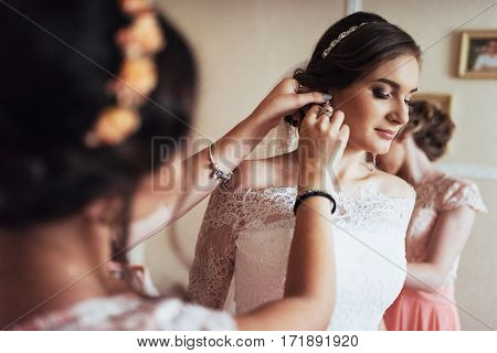Wedding day. Beautiful bride trying on earrings.