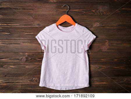 Blank pink t-shirt against wooden background
