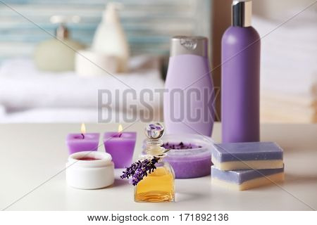 Set of body care cosmetics with lavender and candles on table