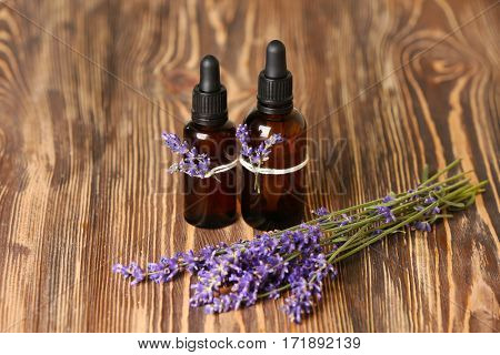 Bottles of essential oil with lavender on wooden background
