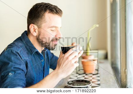 Young Man Enjoying The Smell Of Coffee