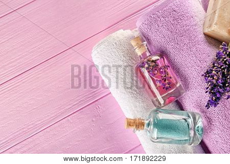 Bottles with lavender aroma oil and natural soap on pink wooden background, closeup