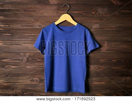 Blank blue t-shirt against wooden background