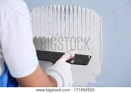 Professional worker making repair in room