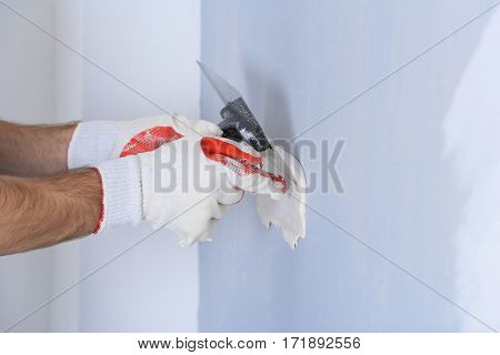 Builder using plastering tool for finishing wall