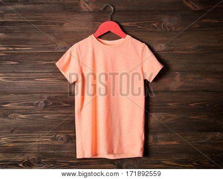 Blank orange t-shirt against wooden background