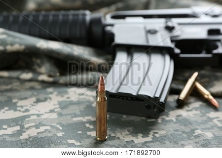 Bullets and rifle on camouflage background