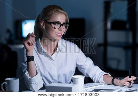Enjoying my responsibilities. Glad cheerful charming secretary sitting in the office and making notes while expressing positivity