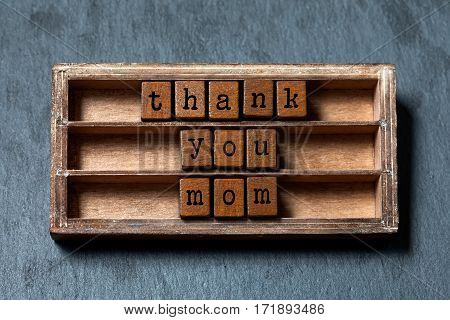Thank you mom quote. Mothers day concept, retro greeting card. Vintage box, wooden cubes phrase with old style letters. Gray stone textured background. Close-up, up view soft focus
