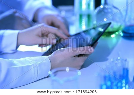 Hands holding tablet in laboratory