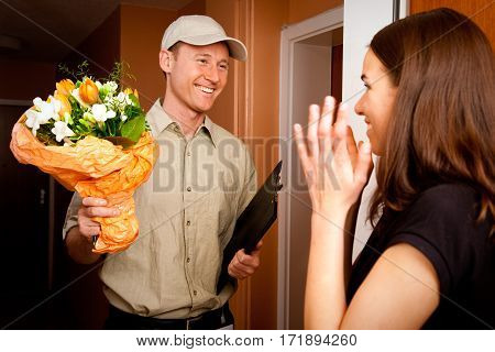 a delivery boy is hading over a bouquet of flowers to a young female customer. focus is on the delivery boy.