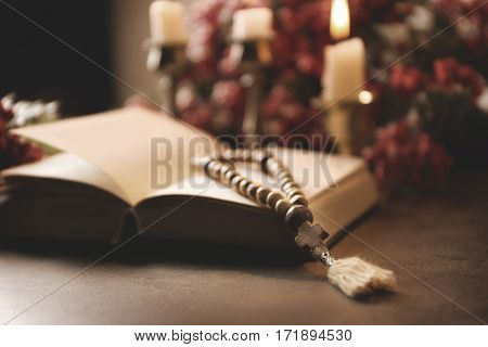 Open Bible and wooden rosary beads on table