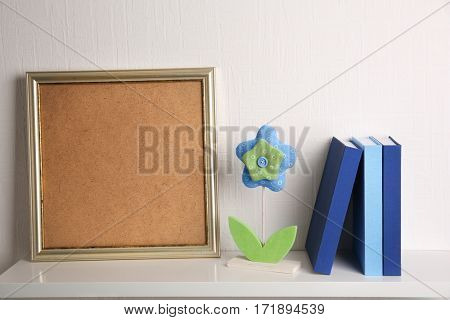 Set of books in row with frame on white wooden shelf