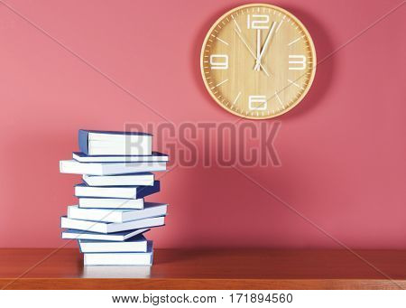 Pile of books on wooden table against pink background