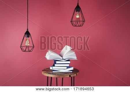 Little table with pile of books and decorative lamps on pink background