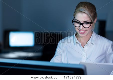 Working on the project. Skillful educated charming businesswoman sitting in the office and using modern devices while expressing joy and interest