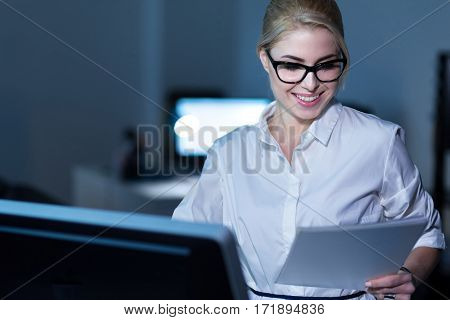 Full attention at work. Smiling delighted pleasant secretary sitting in the office and using gadgets and papers while expressing positivity