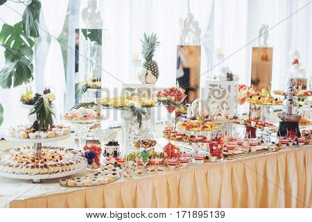 Banquet table full of fruits and berries and an assortment of sweets.