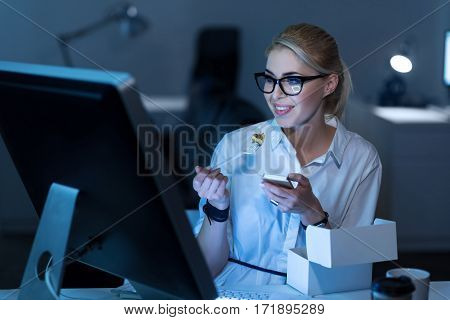 My free minutes at work. Happy young joyful secretary sitting in the office and eating fast food while expressing positivity and holding the phone