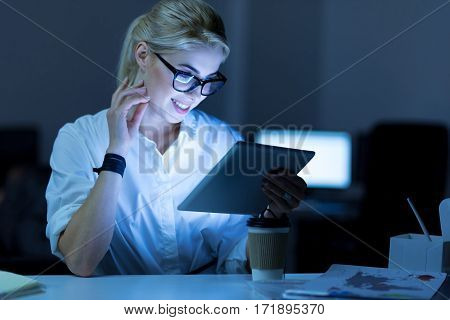 Surfing for new ideas. Positive charming smiling IT woman sitting in the office and using tablet while working on the project