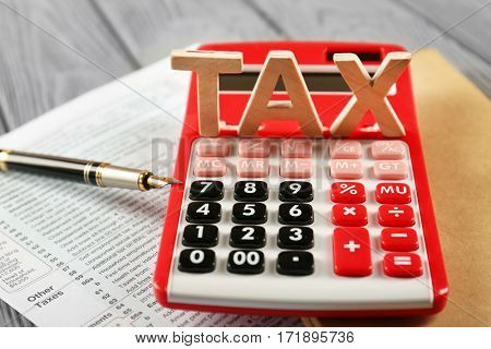 Word TAX and calculator on wooden table