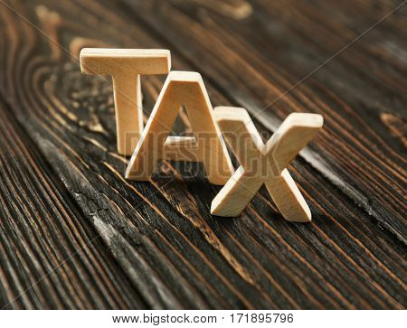 Word TAX on wooden table, closeup