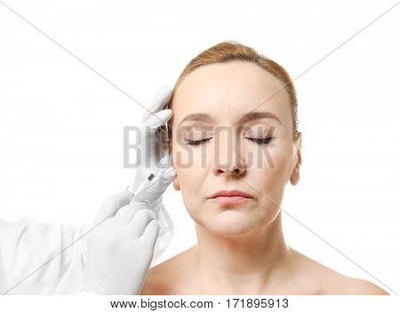 Plastic surgery concept. Mature woman receiving injection on white background