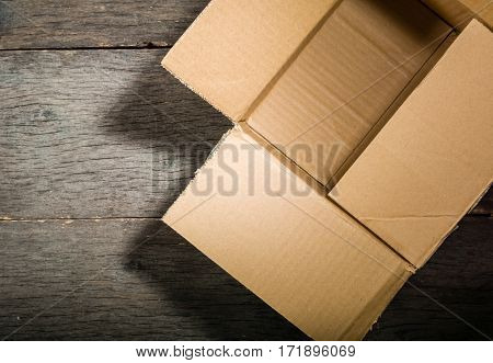 Open Square Cardboard Box On The Background Of The Old Wooden Table.