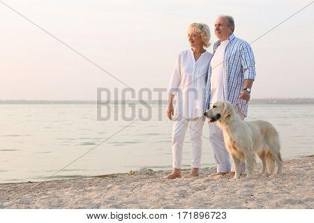 Senior couple and big dog on riverside