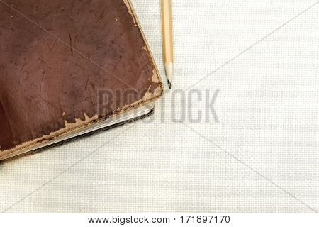 Old leather vintage book with pencil on simple burlap background space for text