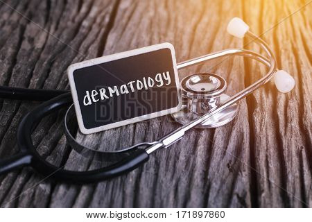 Stethoscope On Wood With Dermatology Word As Medical Concept.