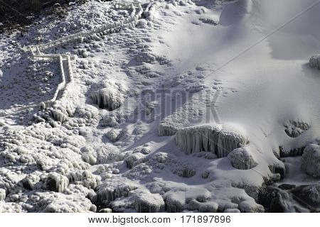 Snow and ice covered stairs path leading up the side of a steep rocky winter mountain adventure travel concept