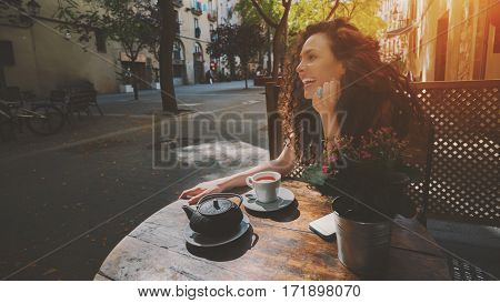Young curly woman with beautiful smile looking away while sitting in cafe during coffee break laughing hipster girl relaxing in street cafe female enjoying good day and drinking tea in street bar