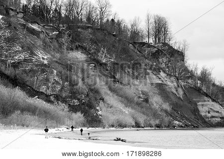 Dramatic view of bluffs overlooking calm winter coastline people walking dogs show grandness of scale
