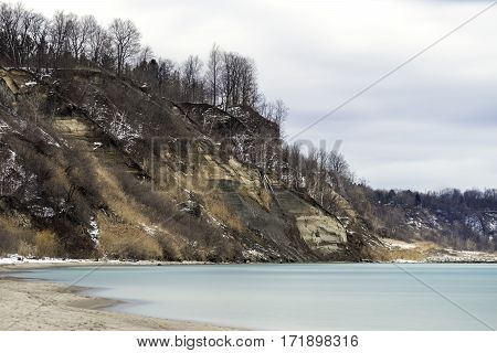 Dramatic bluffs and vast winter landscape overlooking tranquil calm shore