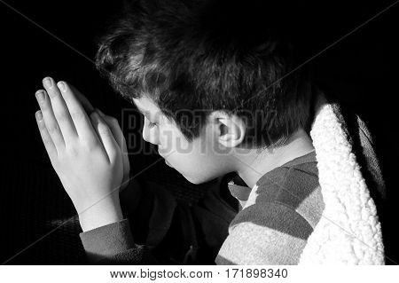 Young boy kneeling to pray at bedtime eyes closed picture of innocent Christian faith religious concept