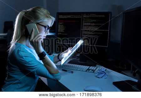 Multitasking person. Charming skilled gifted receptionist sitting in the office and using modern gadgets while expressing concentration and talking over the phone