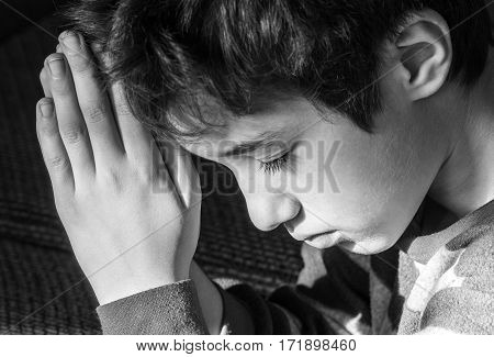 Young boy bowing his head and praying solemnly black and white Christian religious concept